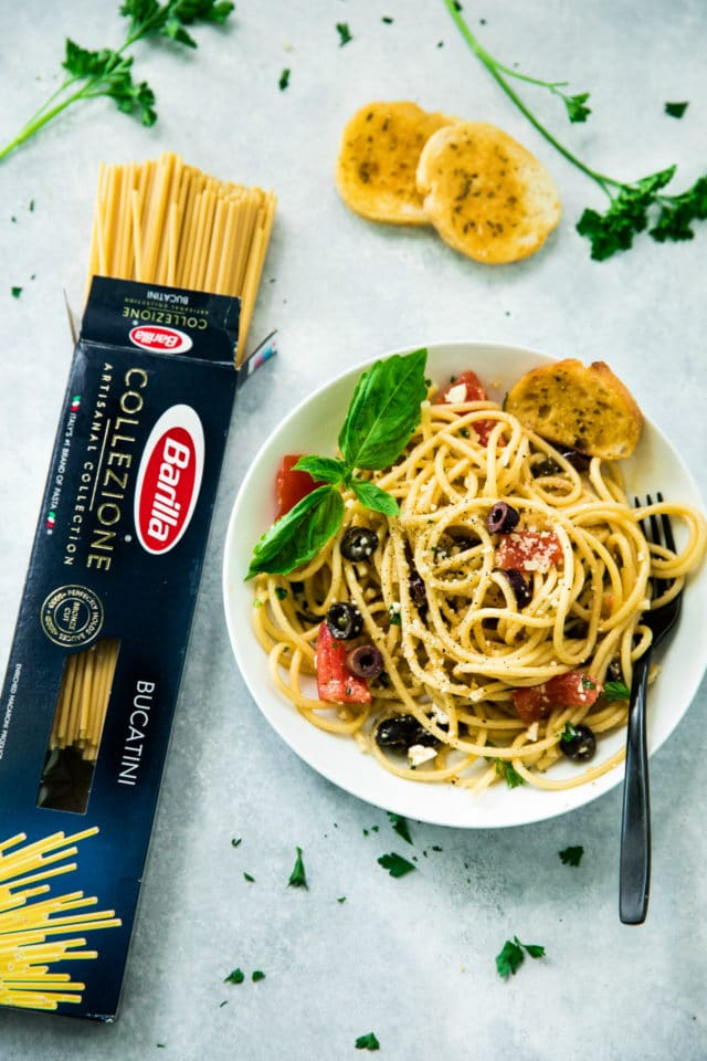 overhead image of Easy Greek Pasta Salad served in a white bowl with a black fork. Barilla pasta box is on the side with slices of garlic bread.