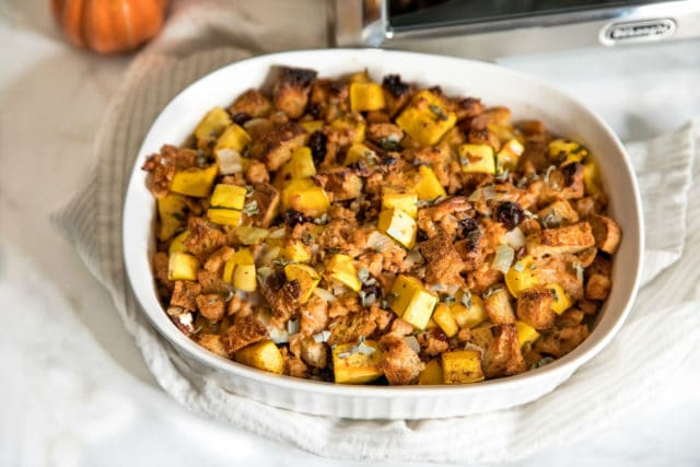 overhead closeup photo of Delicata Squash Stuffing in a white casserole dish on the kitchen counter