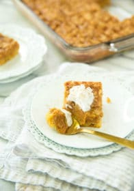 Pumpkin Dessert Squares served on a white plate with a gold spoon and topped with Reddi wip