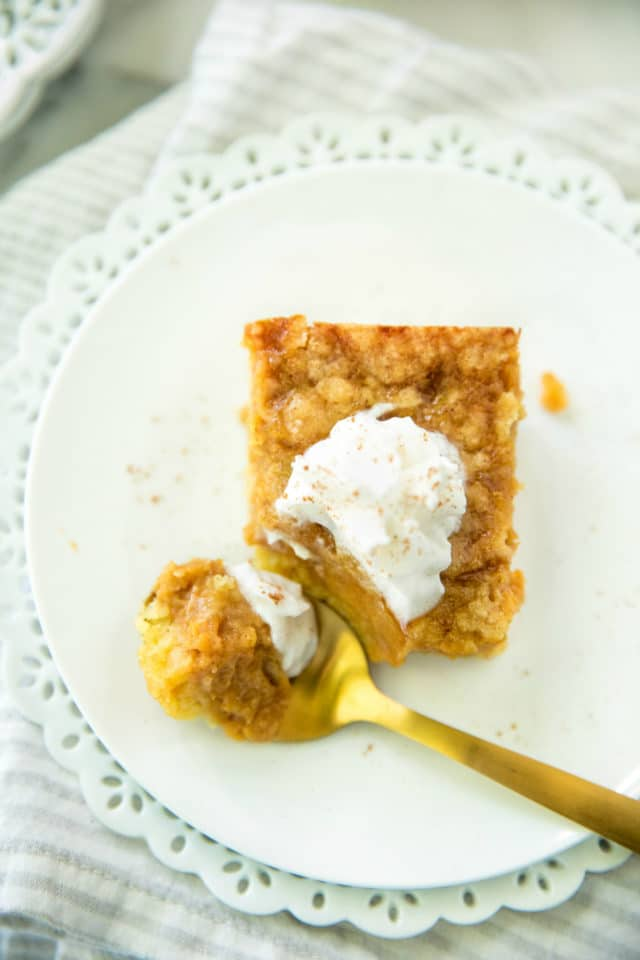 closeup overhead image of Pumpkin Dessert Squares served on a white plate with a gold spoon and topped with whipped cream