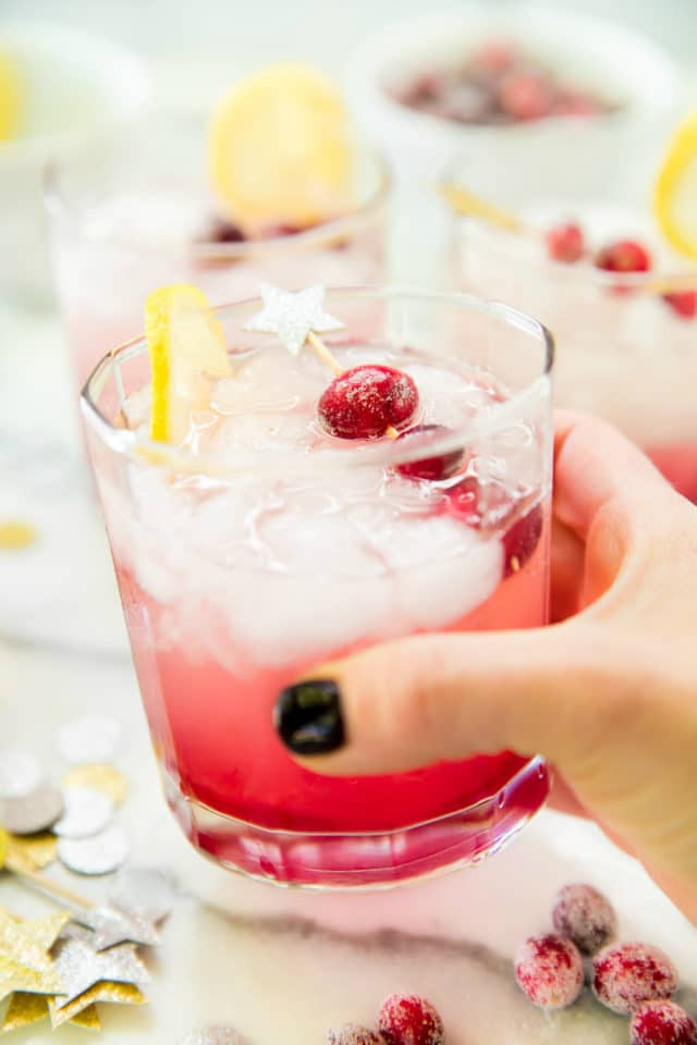 woman's hand holding a cranberry cocktail