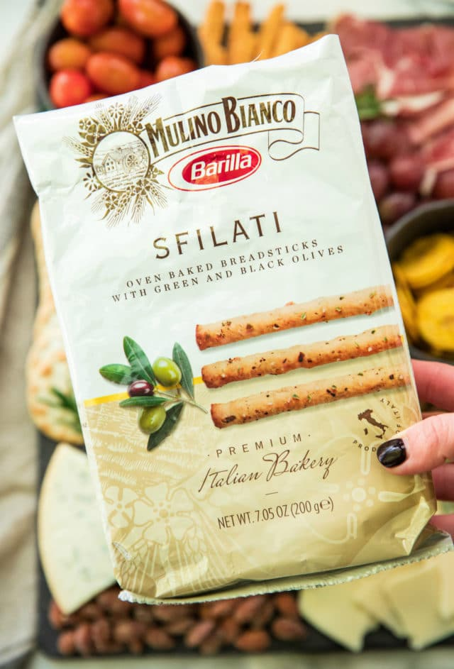 woman's hand holding a package of Mulino Bianco breadsticks