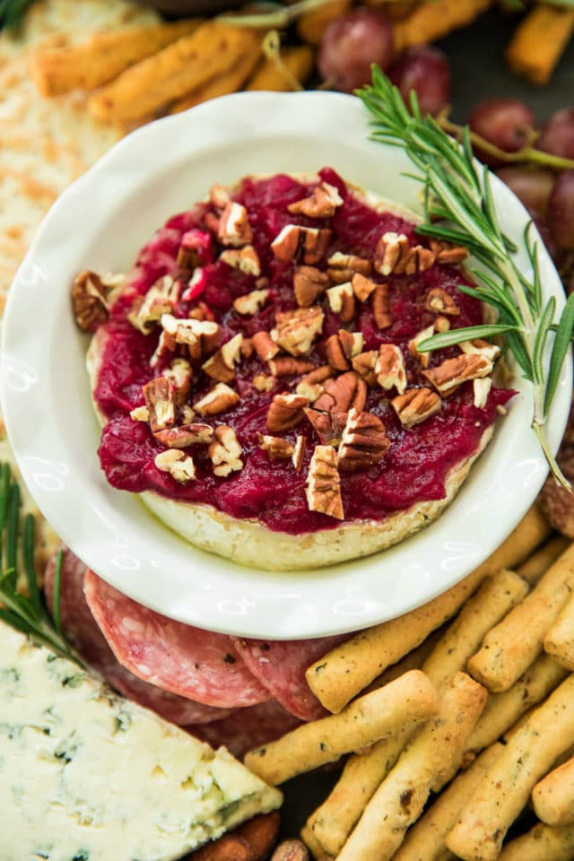 Cranberry sauce baked brie topped with chopped pecans and a sprig of rosemary on the side