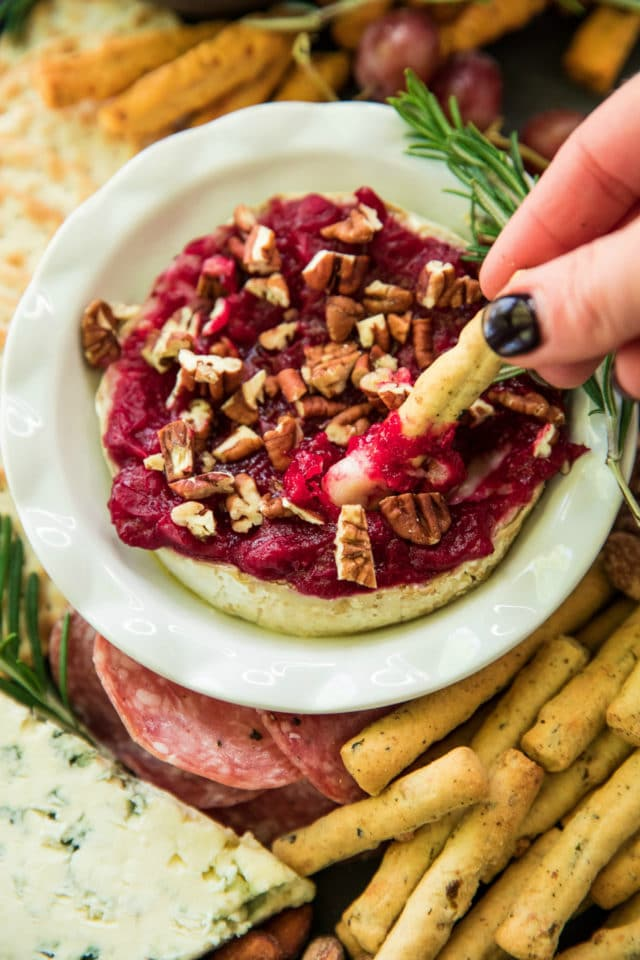 woman's hand dipping a breadstick into cranberry sauce baked brie