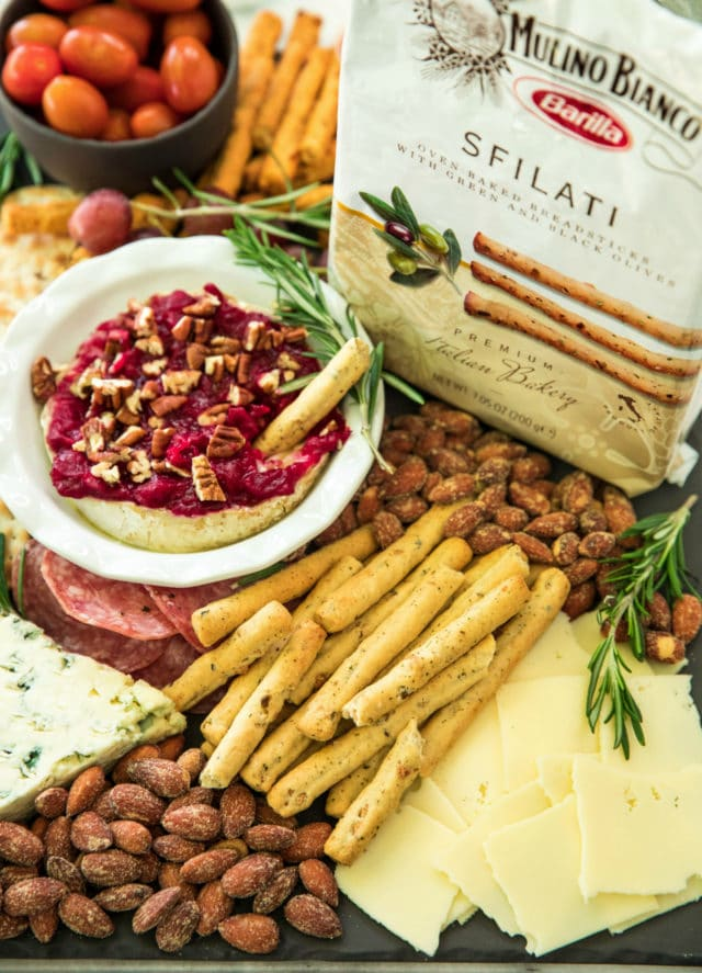 holiday cheeseboard with a breadstick dipped in a cranberry cheese dip