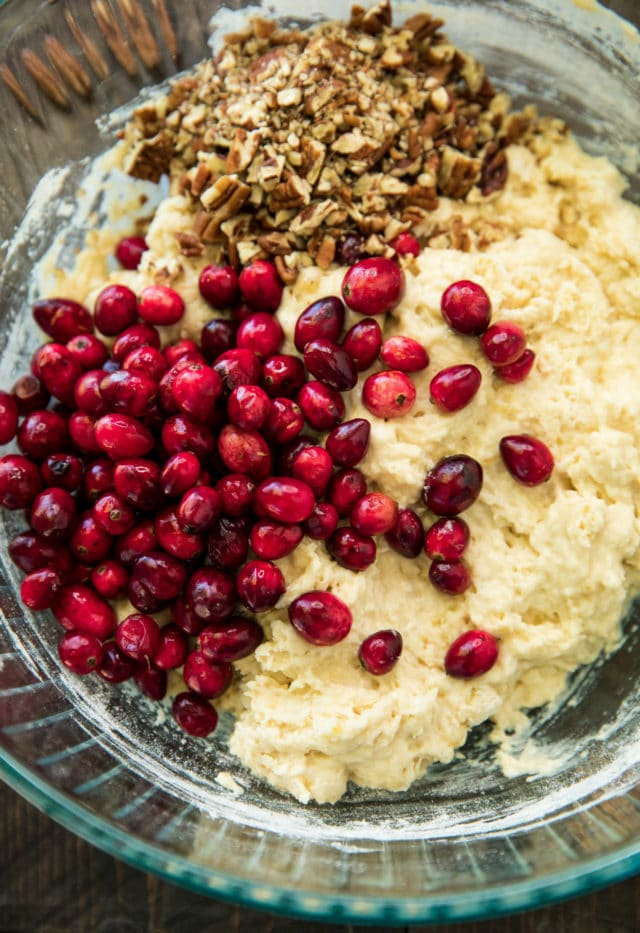 adding fresh cranberries and chopped pecans to cranberry bread batter