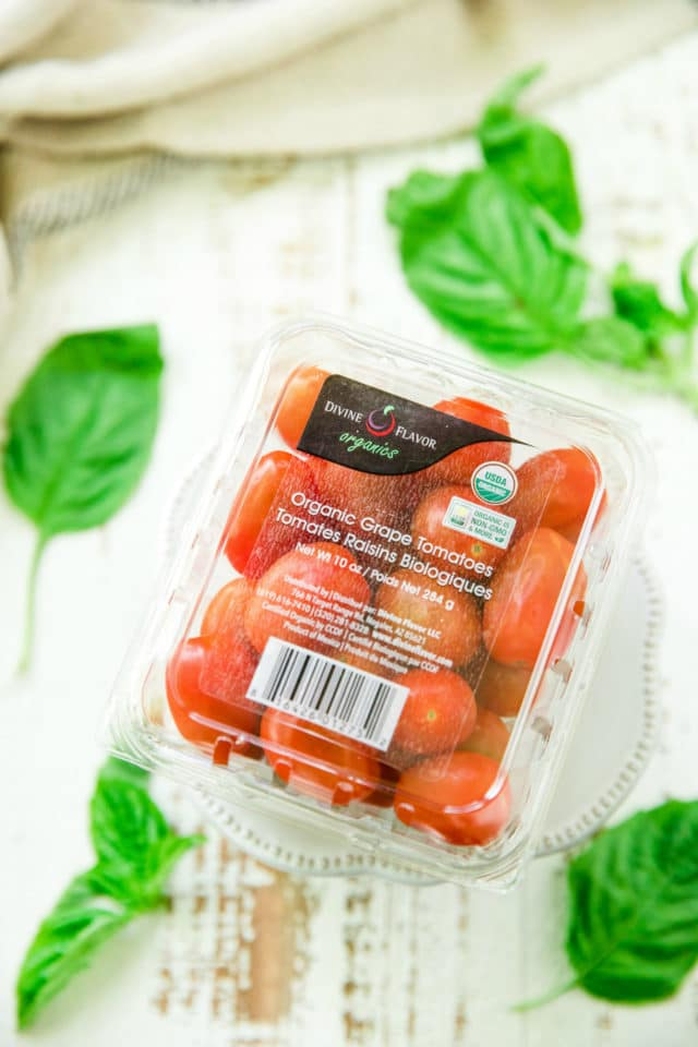 package of divine flavor grape tomatoes alongside fresh basil leaves