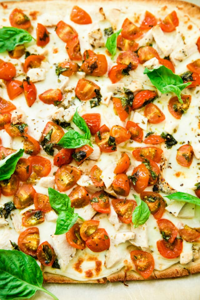 Bruschetta Chicken Alfredo Flatbread topped with fresh basil leaves