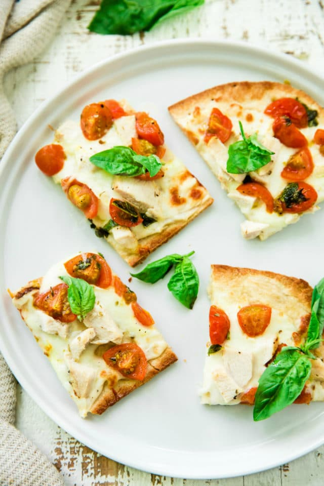 slices of flatbread pizza on a white plate with fresh basil