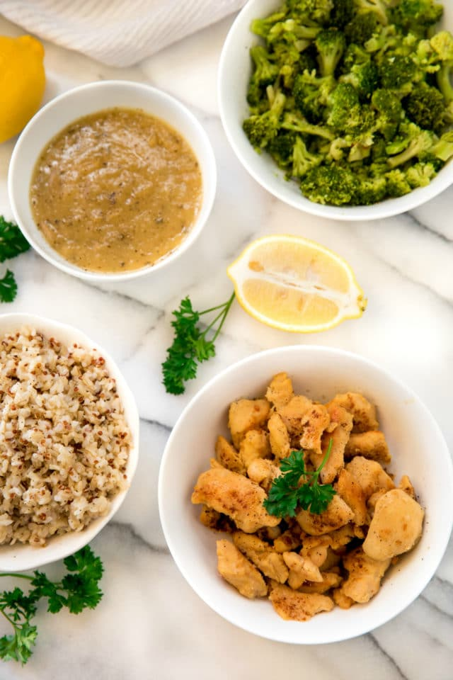 bites of chicken with broccoli and rice served in white bowls