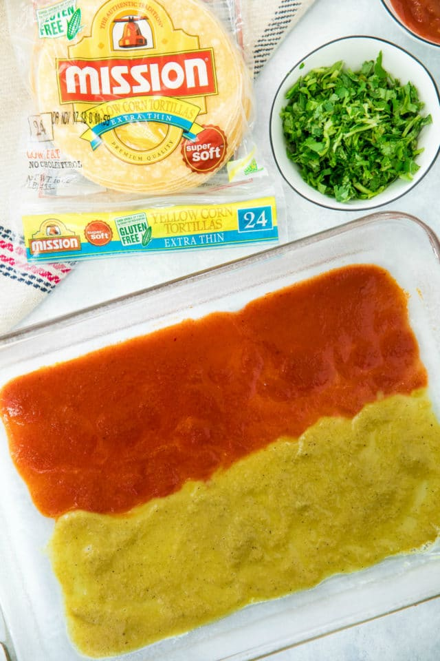 red and green enchilada sauce in a glass baking dish