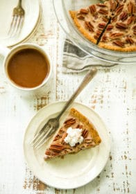 healthy pecan pie topped with whipped cream on a plate with a fork