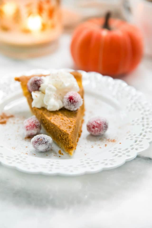 pumpkin pie on a white plate topped with whipped cream and sugared cranberries