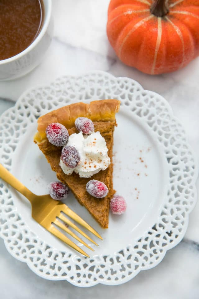 pumpkin pie piece topped with whipped cream and sugared cranberries