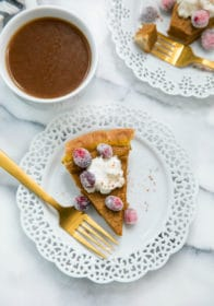 healthy pumpkin pie on a white plate with a gold fork served with coffee