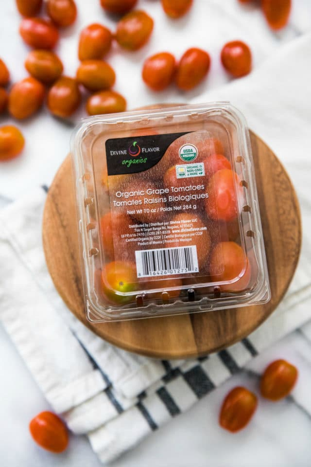 package of grape tomatoes on a wooden platter