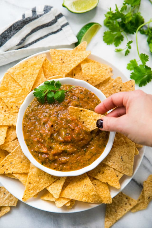 tortilla chip dipping into salsa bowl