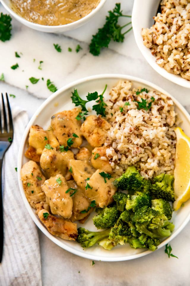 chicken with gravy served with brown rice and broccoli on a white plate