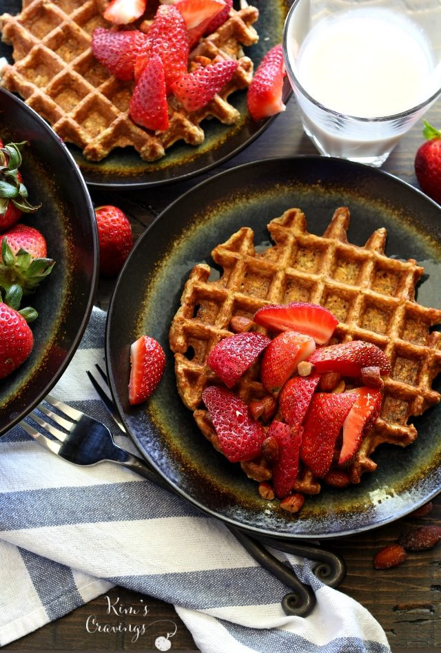 waffles on a black plate topped with strawberries and maple syrup