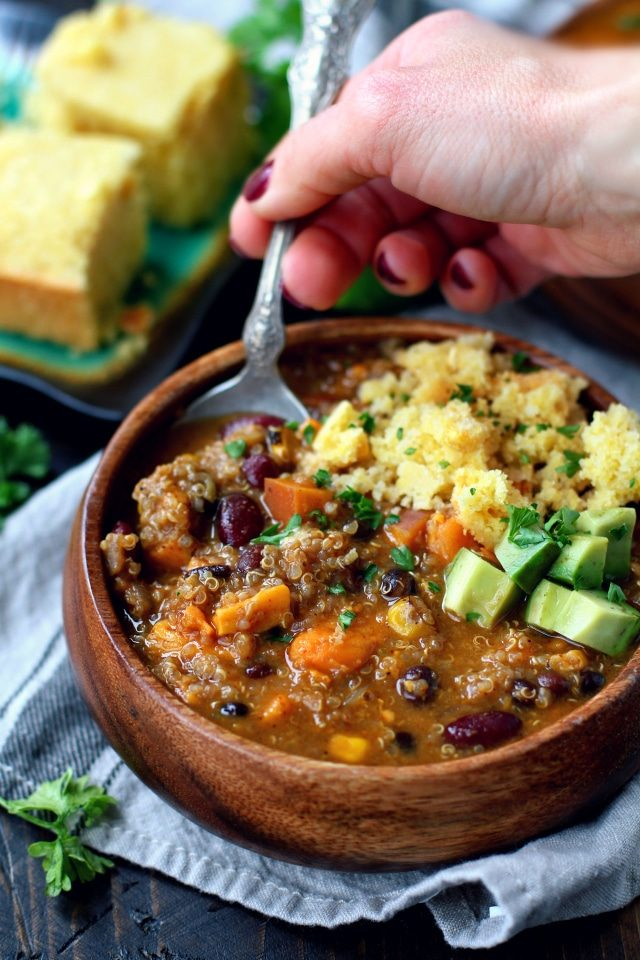 woman's hand spooning out a bite of chili topped with diced avocado and cornbread