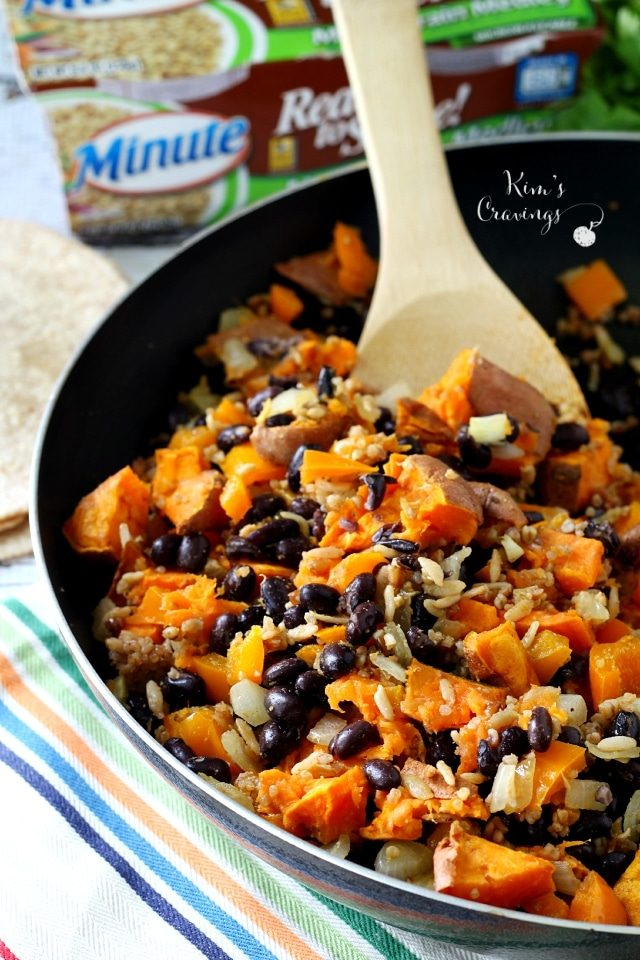 cubed sweet potato, black beans and rice in a skillet with a wooden spoon