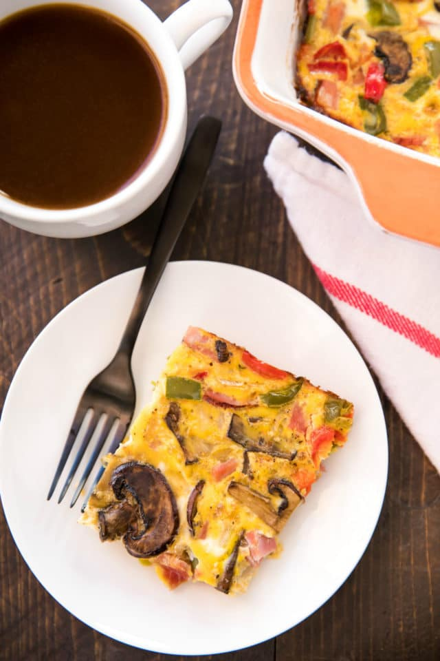 slice of breakfast casserole on a white plate with a black fork, served with coffee