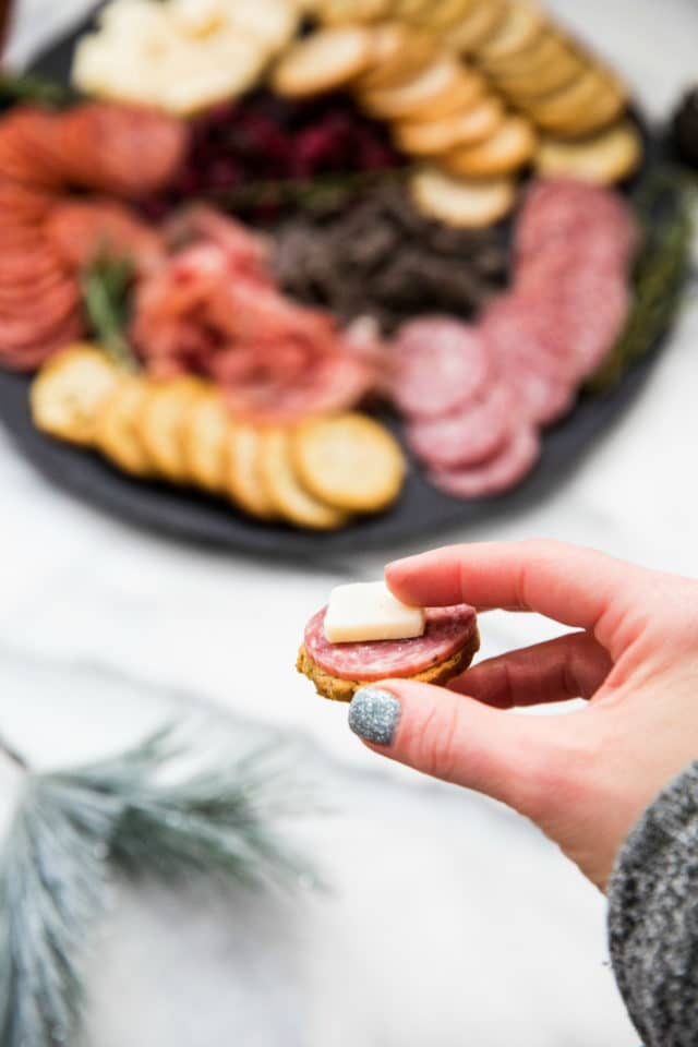 woman's hand holding cracker with meat and cheese