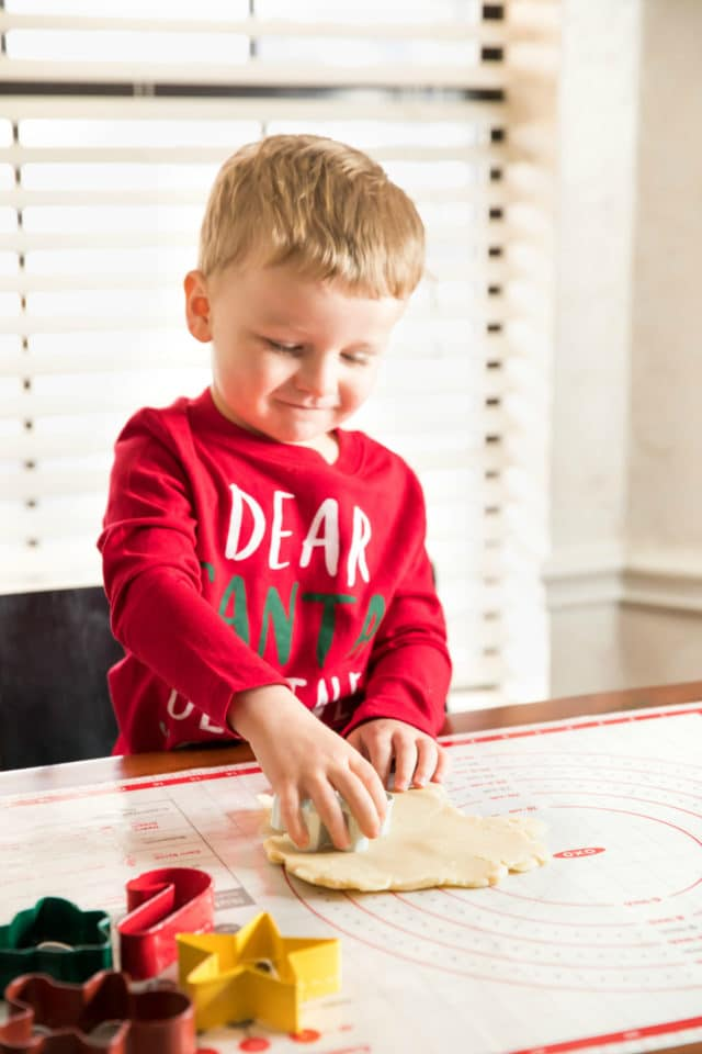 little boy cutting out shapes in sugar cookies
