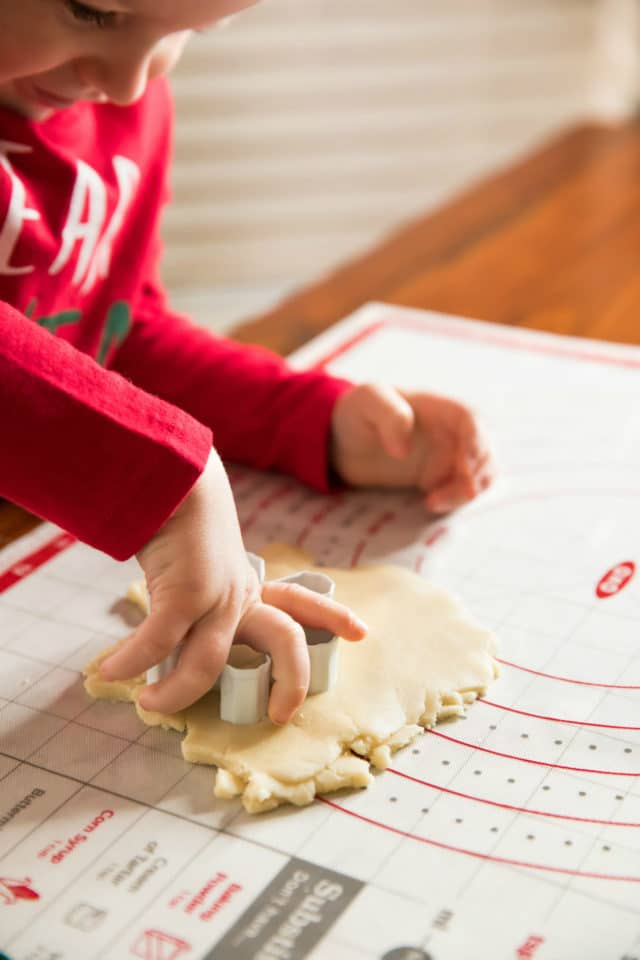 little boy's hand using a cookie cutter to cut out shapes in sugar cookie dough