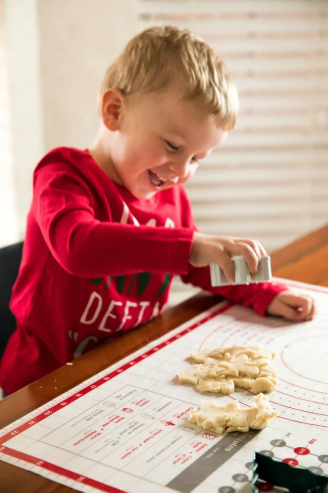 little boy cutting out sugar cookies with cooking cutters