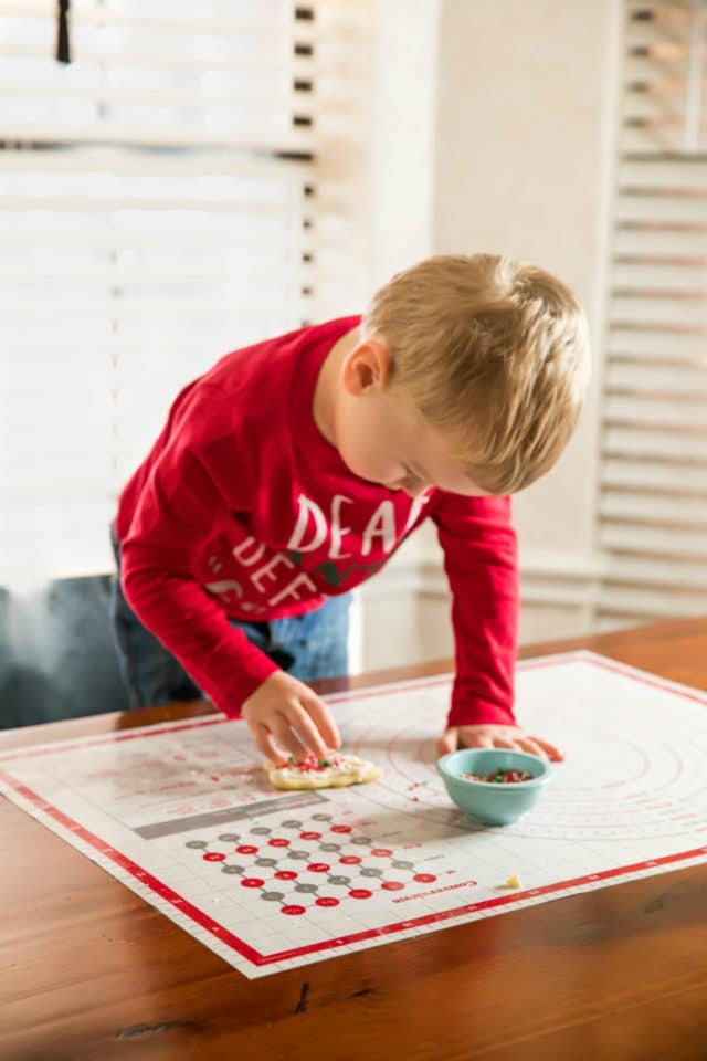 little boy decorating sugar cookies with sprinkles