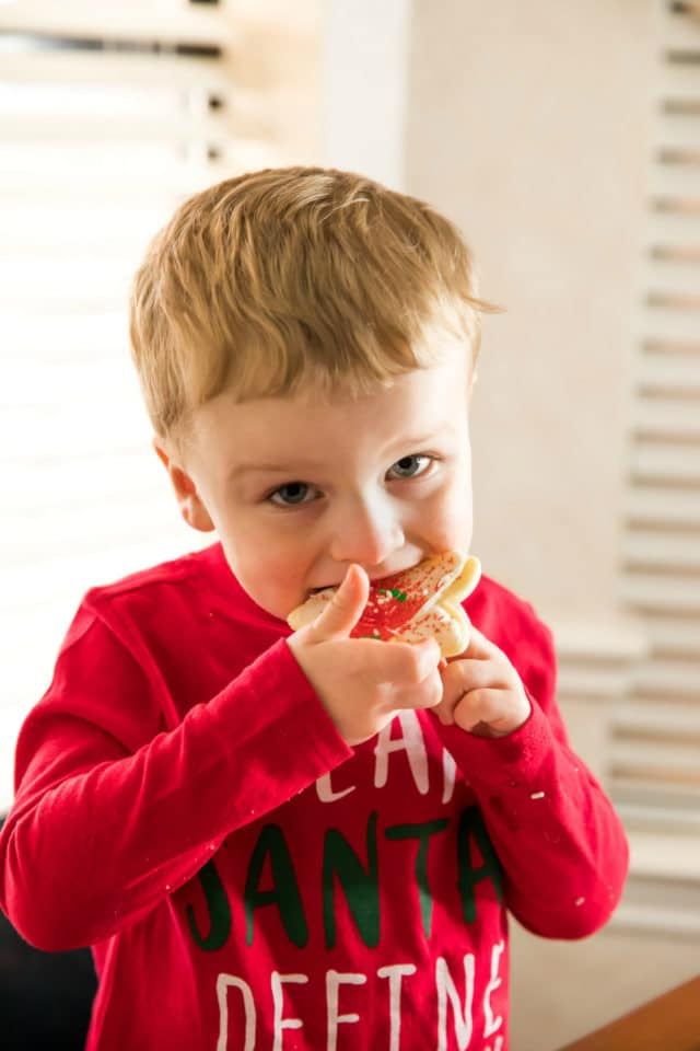 little boy taking a bite of a sugar cookie