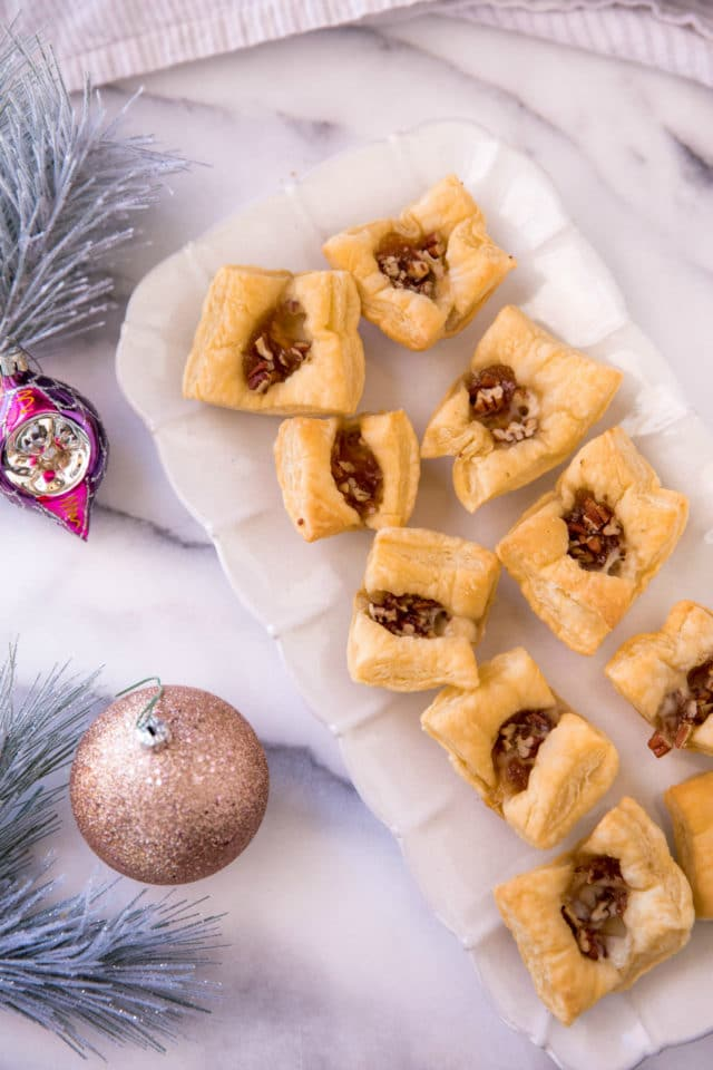 Puff Pastry Brie Bites served on a white serving tray near Christmas ornaments