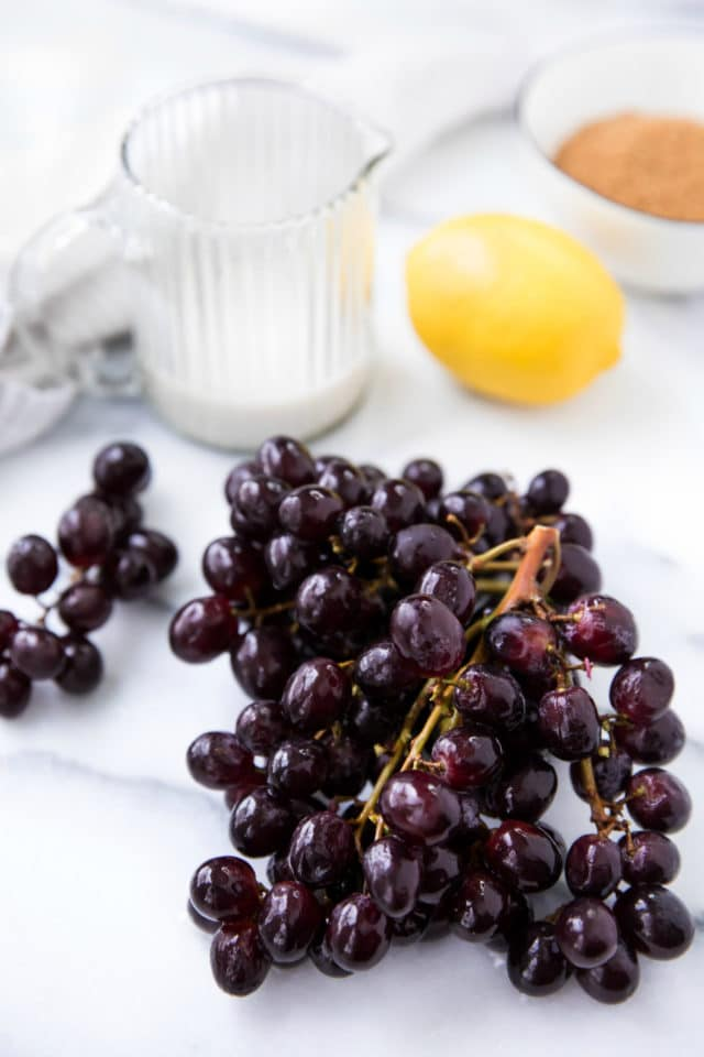 dark red grapes on the vine with a lemon, milk and sugar in the background