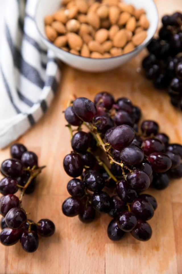 purple grapes on a wooden cutting board and a bowl full of raw almonds