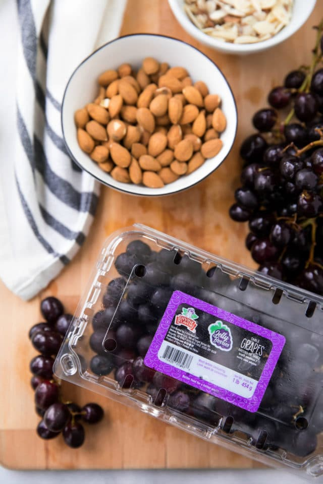 dark purple grapes in a clear container and almonds in a small white bowl