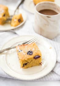 grape cornmeal cake on a white plate served with a cup of coffee