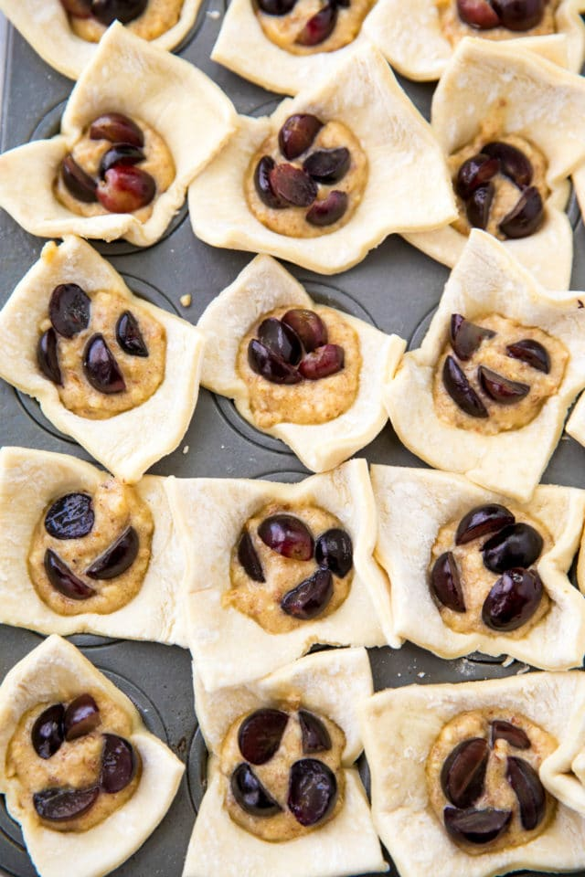 squares of puff pastry dough in mini muffin tins filled with almond filling and chopped grapes