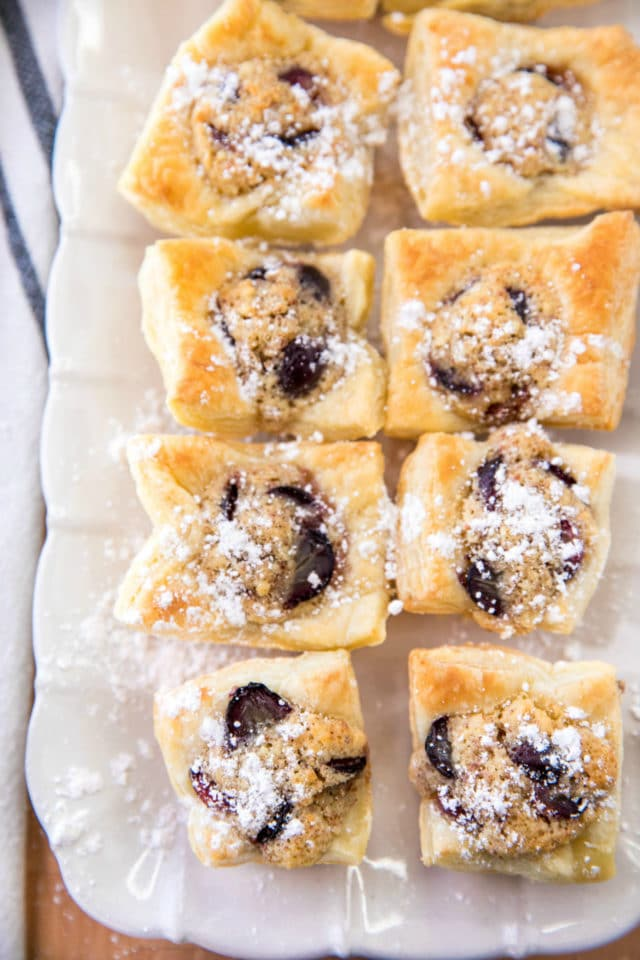 grape almond puff pastry bites on a white serving plate