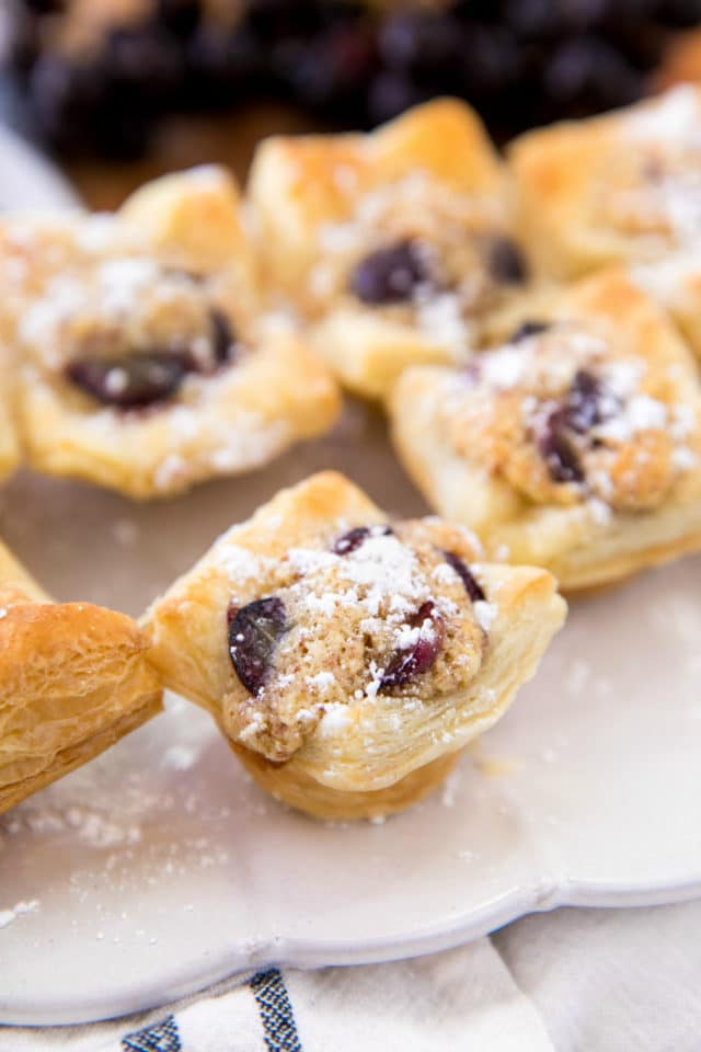grape almond puff pastry bites on a white serving tray dusted with powdered sugar