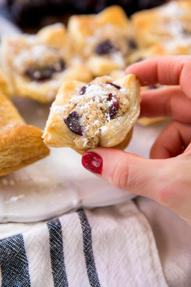 woman's hand holding a grape almond puff pastry bite