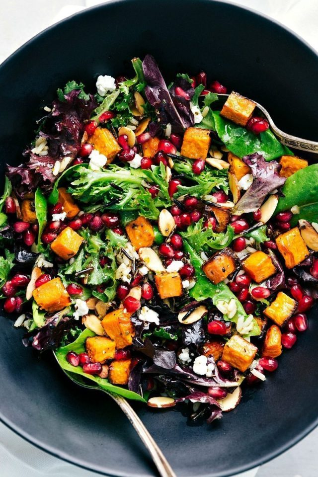 Pomegranate Wild Rice Salad in a black bowl with a silver serving spoon