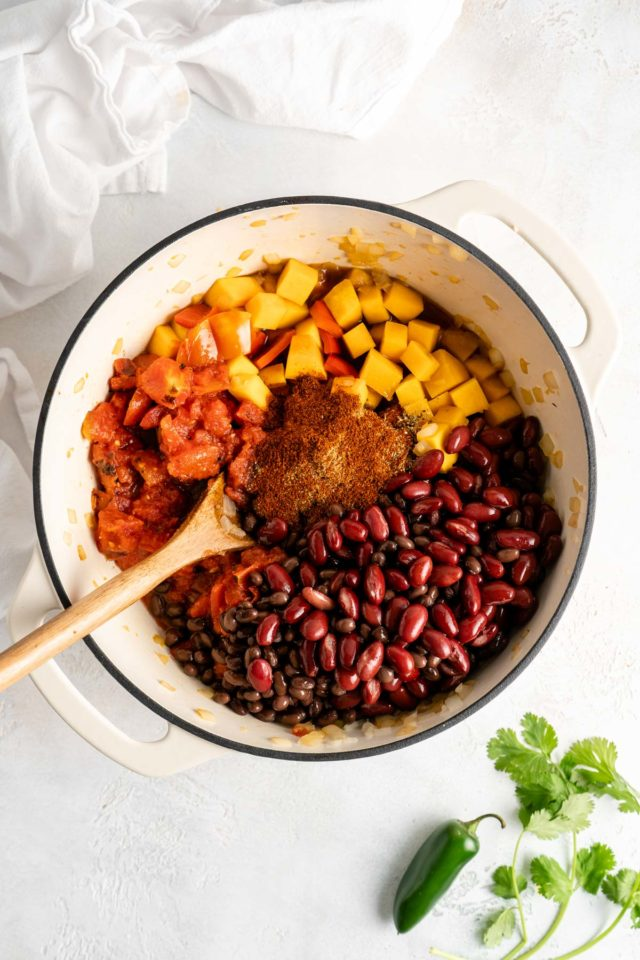 adding spices, beans and tomatoes to large pot