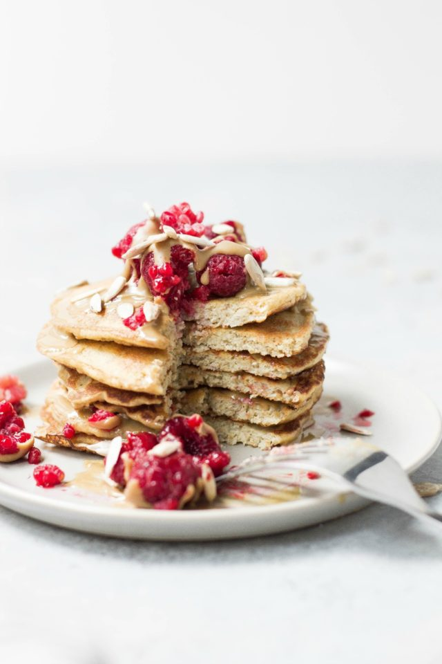 a stack of pancakes topped with raspberries and peanut butter