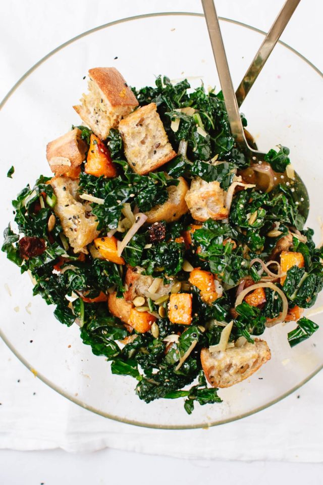 panzanella salad with butternut squash and kale served in a clear salad bowl