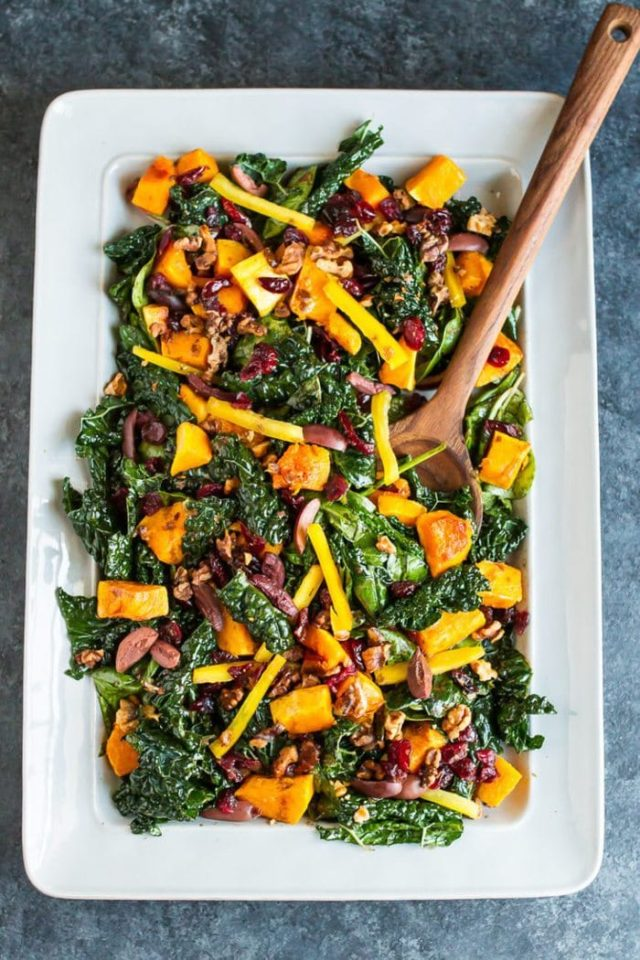 kale butternut squash salad served on a large white serving plate with a wooden spoon