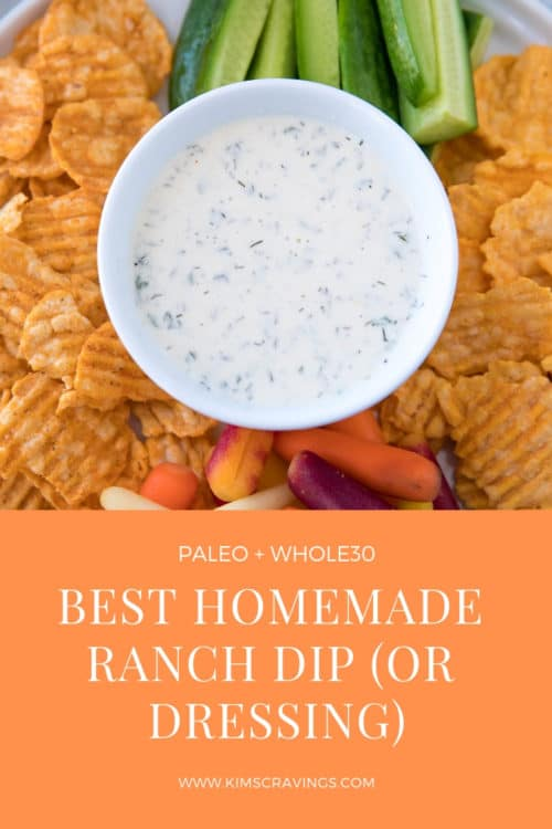 Ranch dip in a small white bowl served with chips and veggies