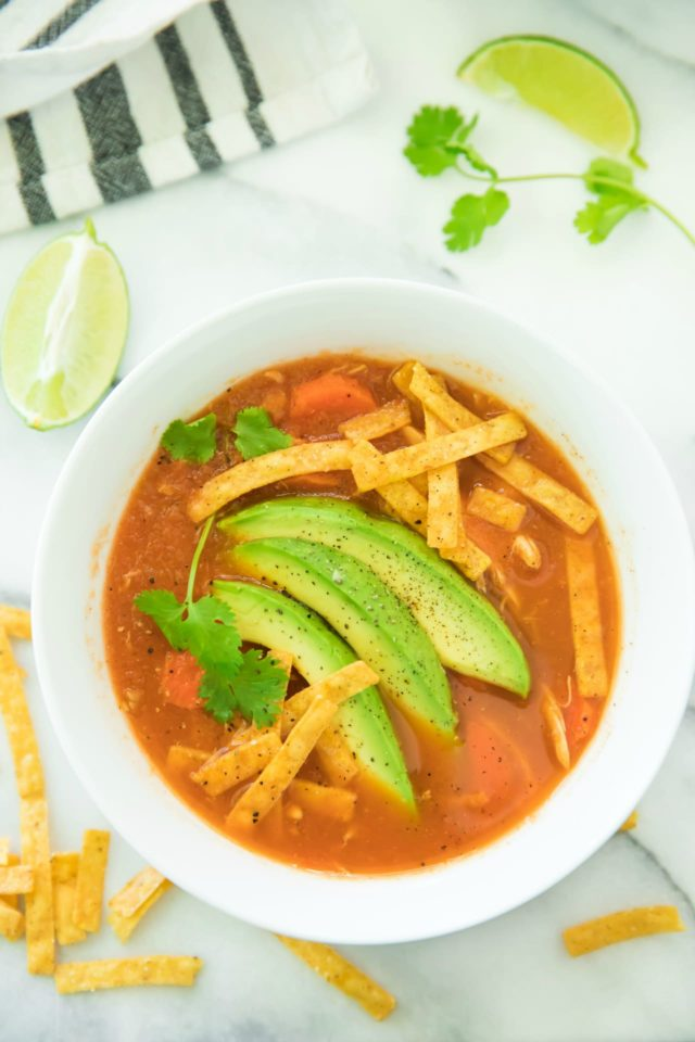 tortilla soup in a white bowl topped with tortilla strips and avocado slices