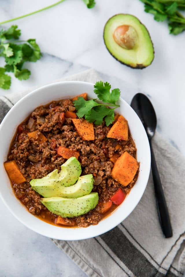 bowl full of beef chili with and avocado and black spoon to the side