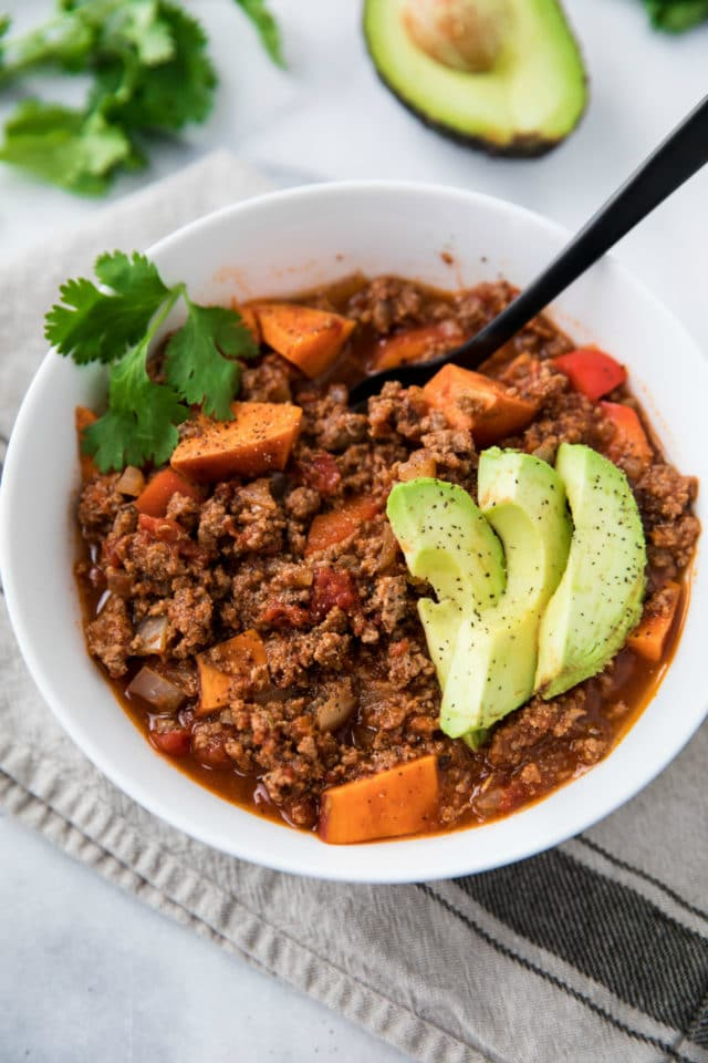 Sweet potato chili in a white bowl topped with slices of avocado